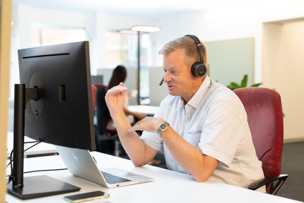 Mitarbeiter mit Headset spricht zu Kunden